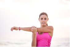 Drawing an arm across the chest to stretch the muscles in the shoulder and arm.